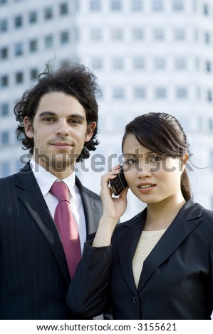 A young businessman and businesswoman standing outside in front of city building
