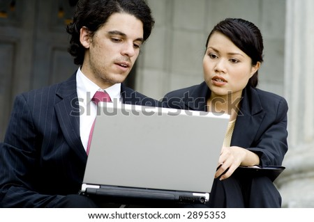 A young businessman and businesswoman working on a laptop computer outside