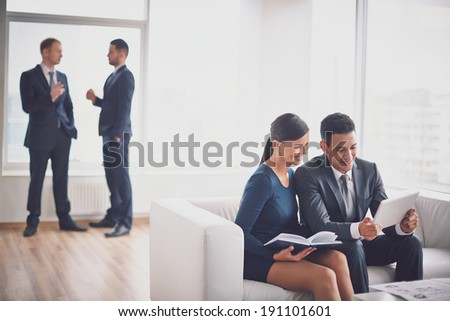 A young businessman and his colleague discussing data in notepad in working environment