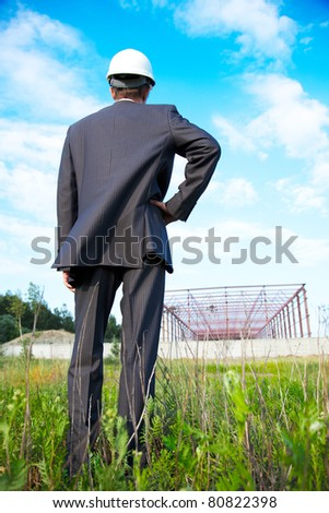 a young businessman at a construction site in the helmet - stock photo