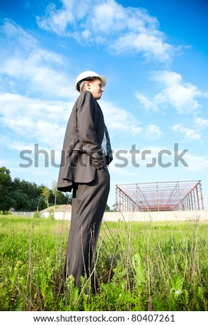 a young businessman at a construction site in the helmet looks like a building is - stock photo