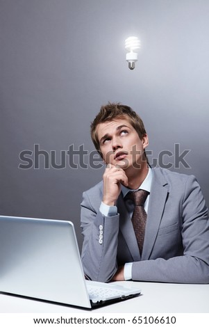 A young businessman at the table looking at a burning light bulb - stock photo