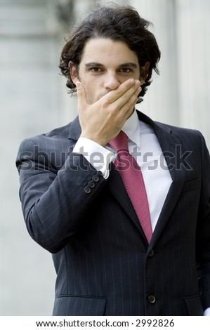 A young businessman covering his mouth with his hand