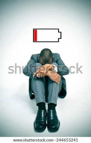 a young businessman curled up in the floor with his head between his knees and an illustration of a low battery