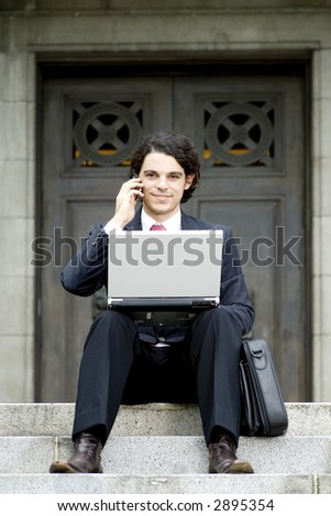 A young businessman doing business on the steps of a building