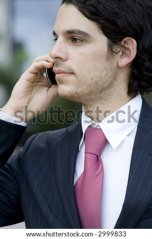 A young businessman holding a mobile phone whilst standing outside