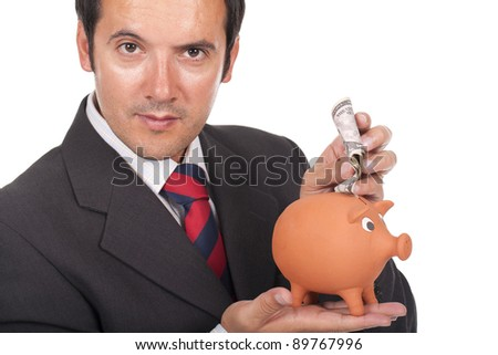 a young businessman holding a piggy bank and putting dollars inside