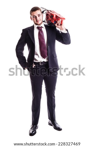 a young businessman holding a red chainsaw isolated over a white background - stock photo