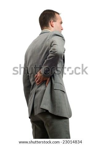 A young businessman holding his back in pain, isolated against a white background - stock photo