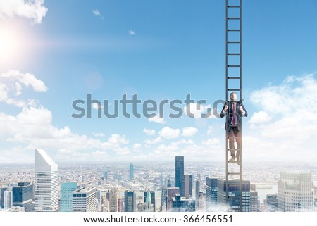 A young businessman in a suit climbing a ladder, Paris view and blue sky at the background. Concept of career development. - stock photo