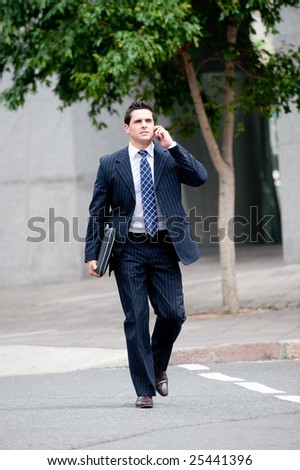 A young businessman in a suit holding mobile phone and crossing road - stock photo