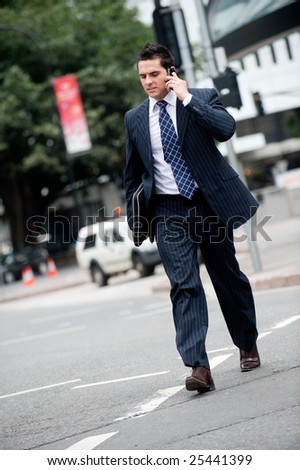 A young businessman in a suit holding mobile phone whilst crossing road - stock photo