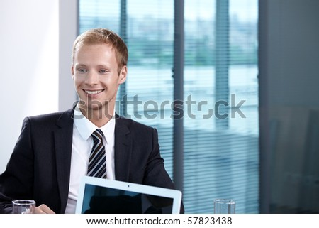 A young businessman in a suit in the office - stock photo