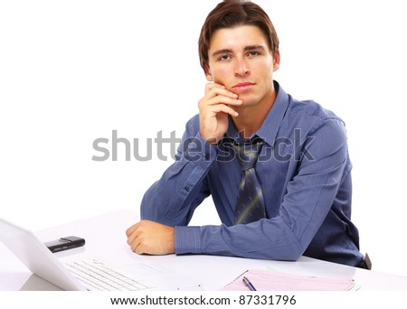 A young businessman in front of a laptop, isolated on white