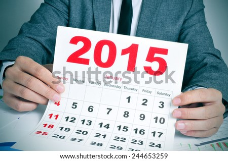 a young businessman in his office desk showing a 2015 calendar - stock photo