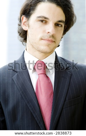 A young businessman in suit and tie shot outdoors (shallow depth of field used)