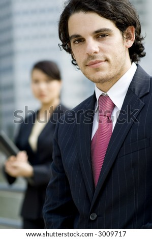 A young businessman in suit standing in front of female colleague