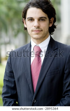 A young businessman in suit standing outside (shallow depth of field used)