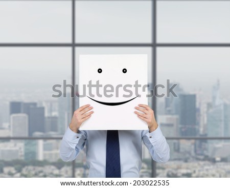 A young businessman is holding a cardboard with a smiley face on it in front of his head. City view background.
