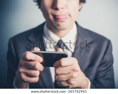 A young businessman is playing mobile games on his smartphone - stock photo