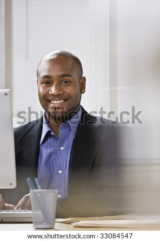 A young businessman is seated at a desk in front of a computer, and is smiling at the camera. Vertically framed shot. - stock photo