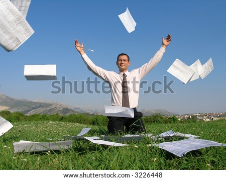 A young businessman is sitting on his knees on a grass and throwing away his papers
