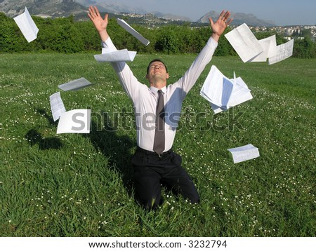 A young businessman is sitting on his knees on a grass and throwing away his papers - stock photo