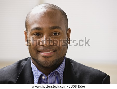 A young businessman is smiling at the camera.  Horizontally framed shot. - stock photo