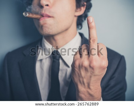 A young businessman is smoking a cigar and is displaying a rude gesture - stock photo