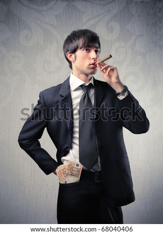 A young businessman is smoking his cigar