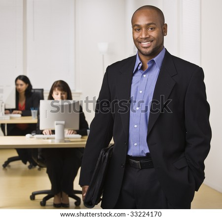 A young businessman is standing in an office with some other business people.  He is smiling at the camera.  Horizontally framed shot. - stock photo