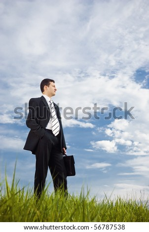 A young businessman is staying outdoors with briefcase in his hand on a very cloudy background