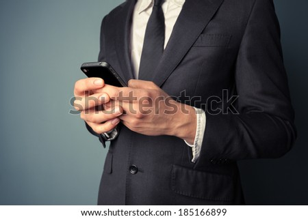 A young businessman is using his smart phone