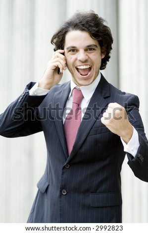 A young businessman is very happy with his phone conversation