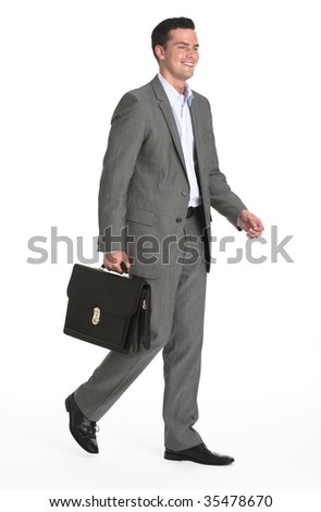 A young businessman is walking and holding a briefcase.  He is smiling and looking away from the camera.  Vertically framed shot. - stock photo
