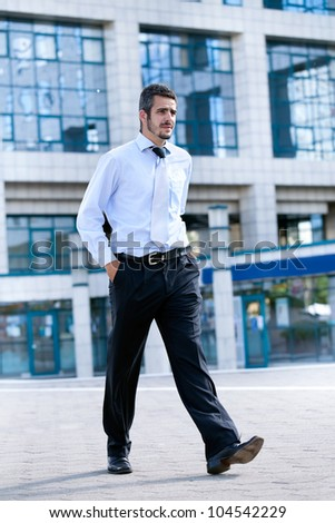 A young businessman is walking and holding hands in pockets