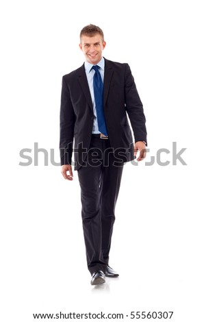 A young businessman is walking. He is smiling and lookingto the camera. isolated over white background