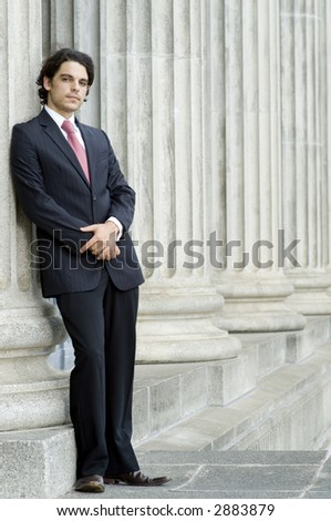 A young businessman leaning against a column of an old building