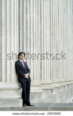 A young businessman leaning against stone pillar