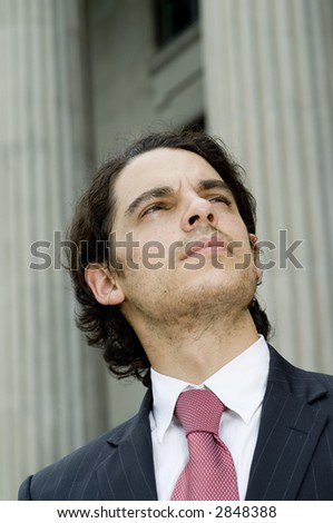 A young businessman looking as if he is deep in thought