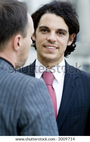 A young businessman looking at the camera standing next to a colleague