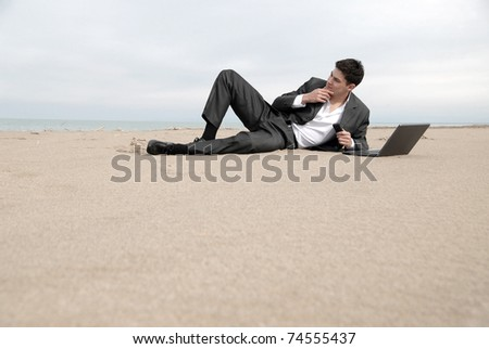 A young businessman lying on the beach in front of a laptop, he thought.