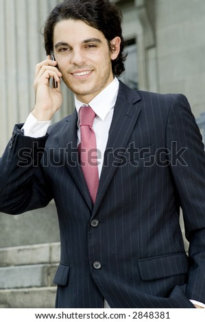 A young businessman making a call on his mobile phone outside
