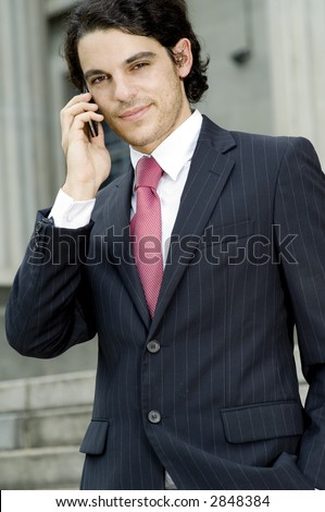 A young businessman making a call on mobile phone outside