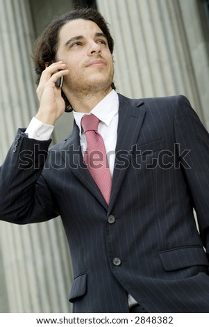 A young businessman making a call outside in front of grand building (shallow depth of field)