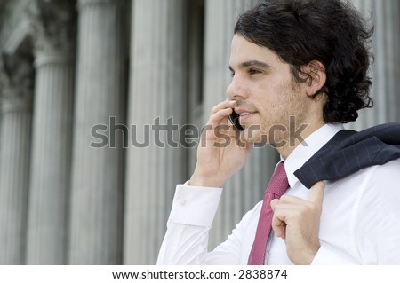 A young businessman making a phone call in front of a grand building
