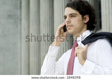 A young businessman making a phone call in front of an old building (shallow depth of field used)