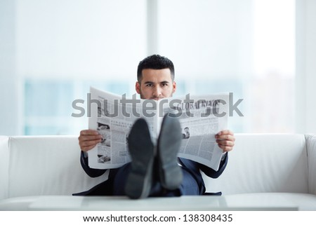 A young businessman on sofa looking at camera while reading newspaper - stock photo