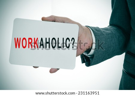 a young businessman showing a signboard with the word workaholic written in it - stock photo