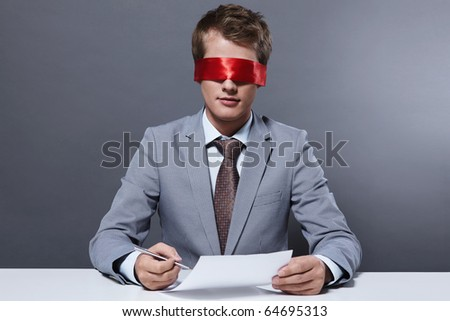 A young businessman signs a contract with a blindfold - stock photo